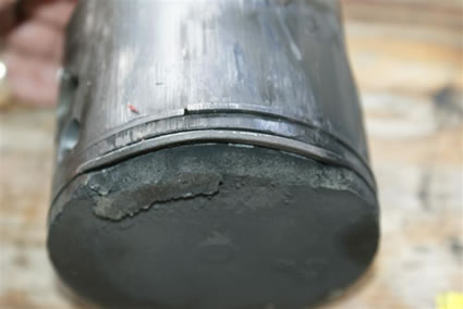 piston exhibits detonation and dome fracture with adhesive scoring to skirt